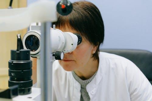 Unrecognizable female scientist watching through slit lamp microscope