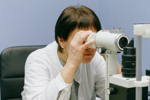 Woman in White Dress Shirt Using White Microscope