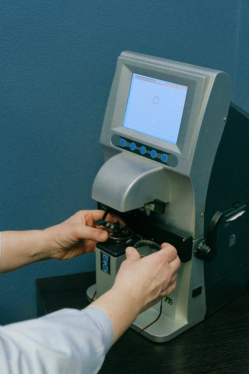 Crop unrecognizable ophthalmologist using keratometer in clinic