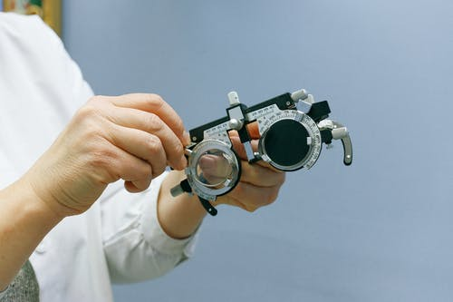 Crop anonymous medic showing ophthalmic device