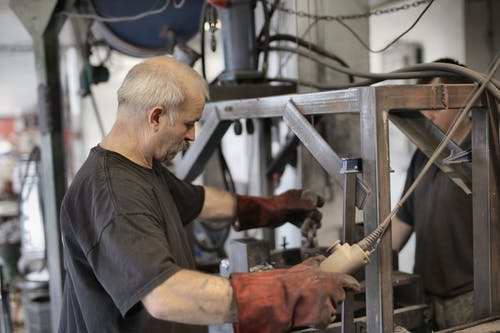 Side view of senior white hair craftsman in heavy duty gloves dealing with machine in workshop