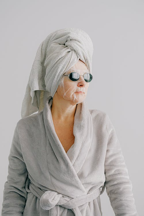 Relaxed woman in bathrobe sheet mask and sunglasses