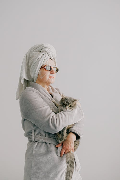 Woman after bath standing with cat in arms