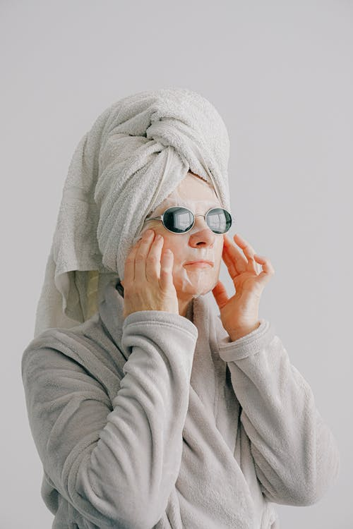 Calm woman with sheet mask on face touching face in bathrobe and towel on head while resting after bathing and looking away