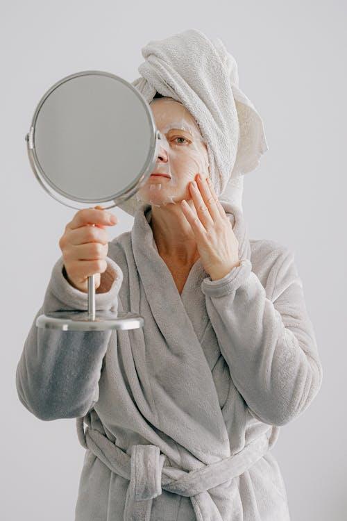 Person in Gray Bathrobe Holding Round Mirror