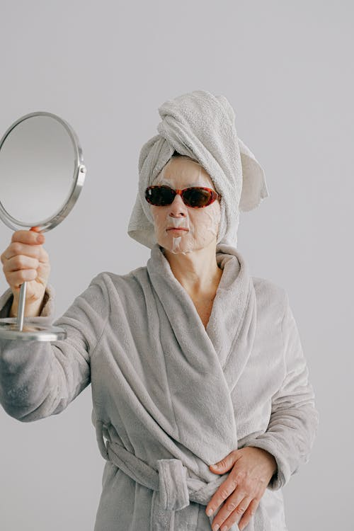 Stylish woman in home clothes with face mask looking in mirror