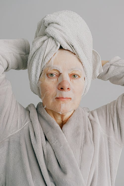 Unemotional woman in sheet mask after bath