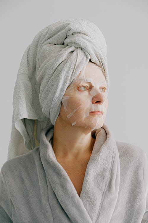 Charming calm woman with towel on head in bathrobe standing with sheet mask on face enjoying healthy morning and looking away