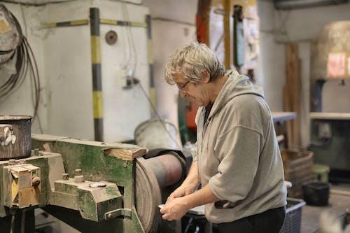 Senior white hair worker grinding detail on machine