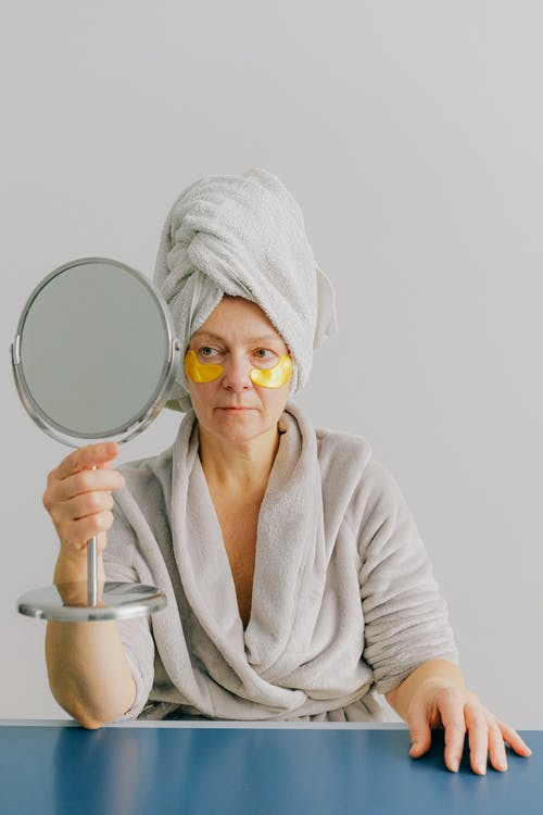 Pensive female in bathrobe with white towel on head sitting at table after bath at home with gold eye patches under eyes while holding table mirror in hands and looking in mirror