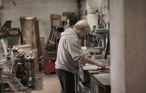 Senior white hair master handling detail on workbench