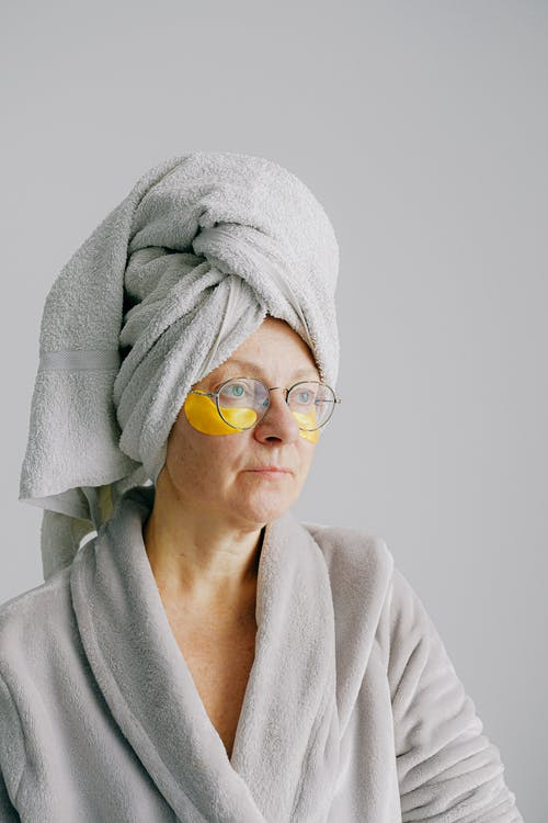 Aged woman in eye patches and eyeglasses