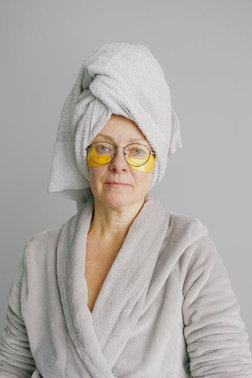 Senior woman with eye patches and eyeglasses after shower