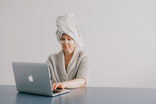 Woman With Towel On Her Head While Using A Laptop