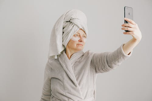 Woman in Gray Bathrobe Holding Black Smartphone