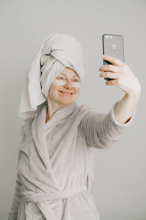 Woman in Gray Bathrobe Holding Iphone