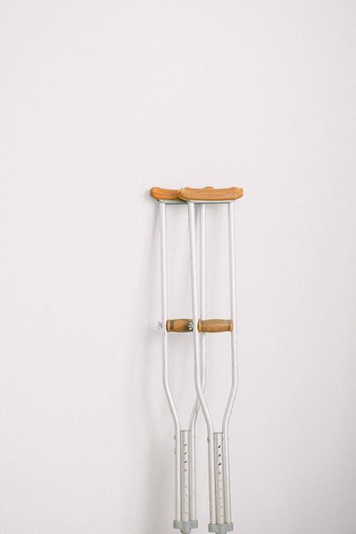 Crutches against light white wall