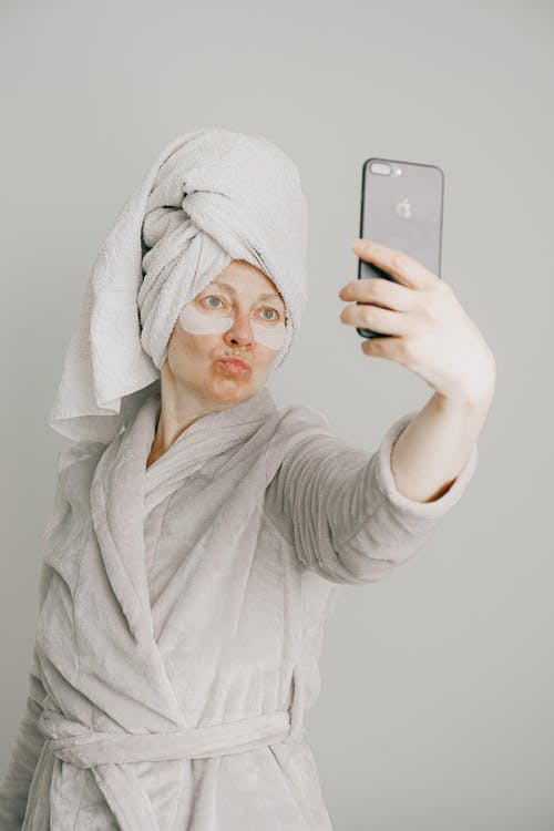 Woman in Gray Bathrobe Holding Iphone 6