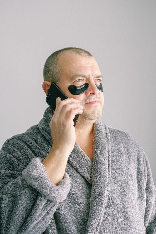Man in Gray Bathrobe Wearing Black Eye Mask
