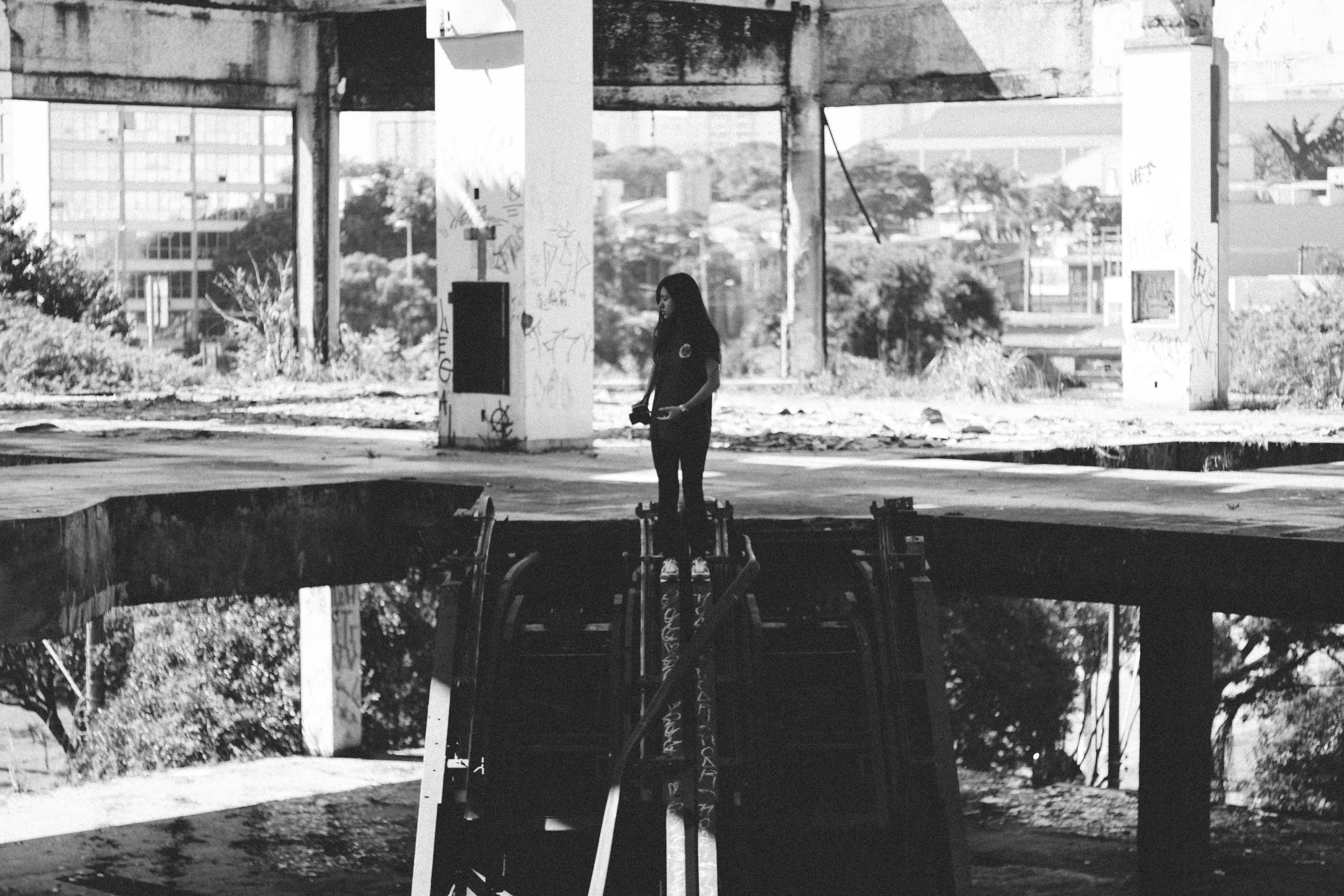 Grayscale Photo of Girl Standing on Concrete Pavement