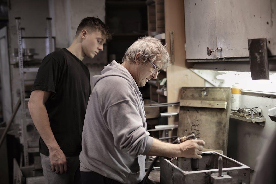 Master showing apprentice how handling detail