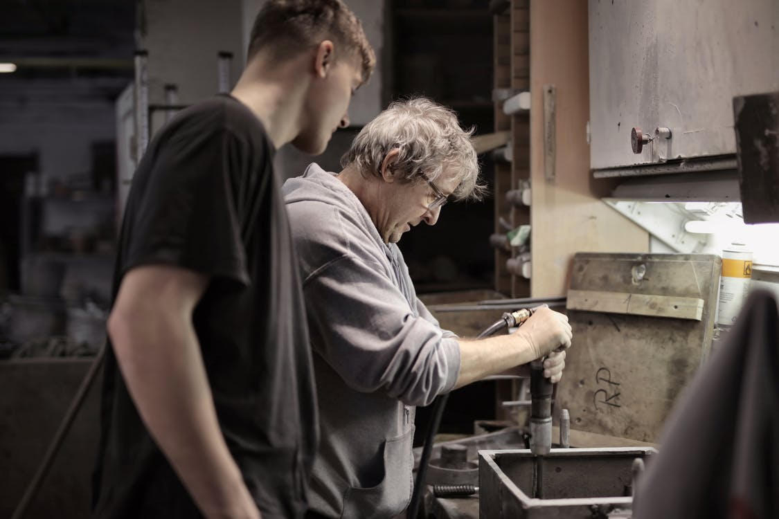 Foreman teaching apprentice working with tools