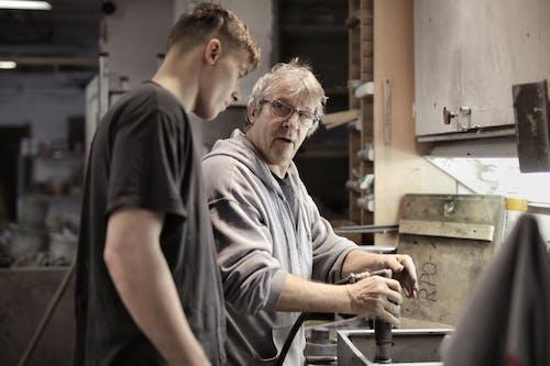 Workers handling detail by pneumatic tool in workshop