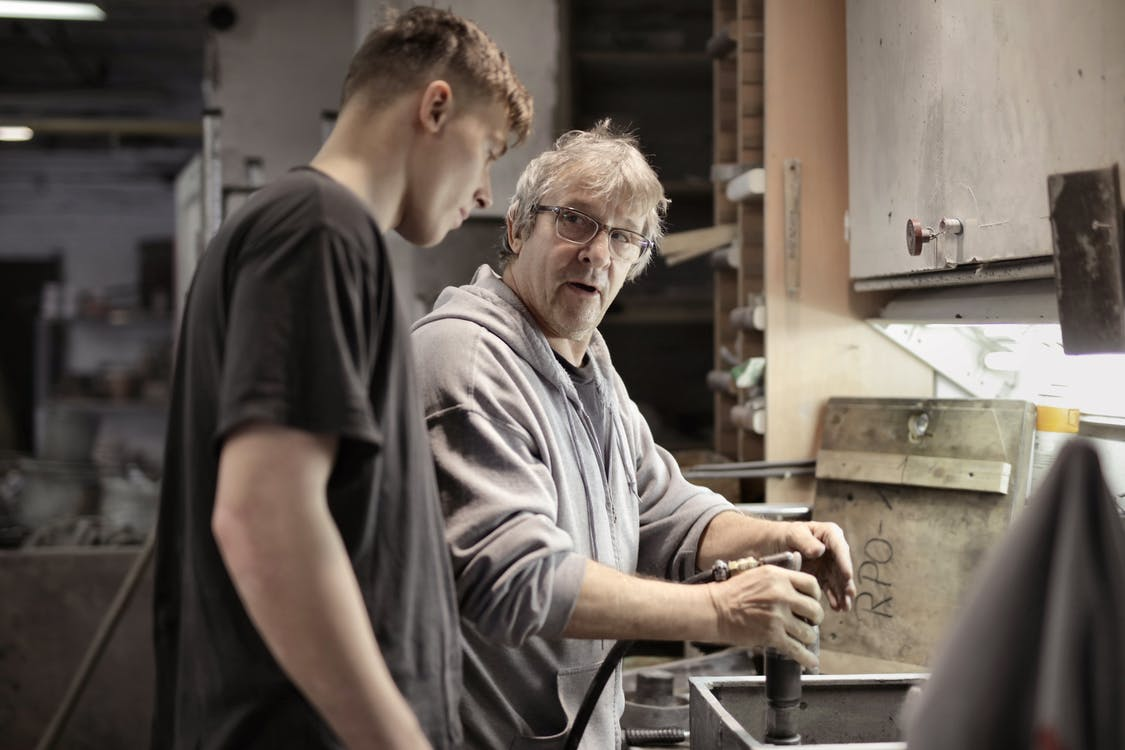 Side view of senior foreman in eyeglasses showing to trainee how handling detail in workshop