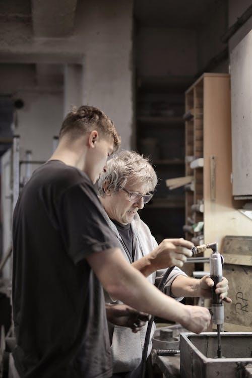 Apprentice helping master assembling detail in workshop