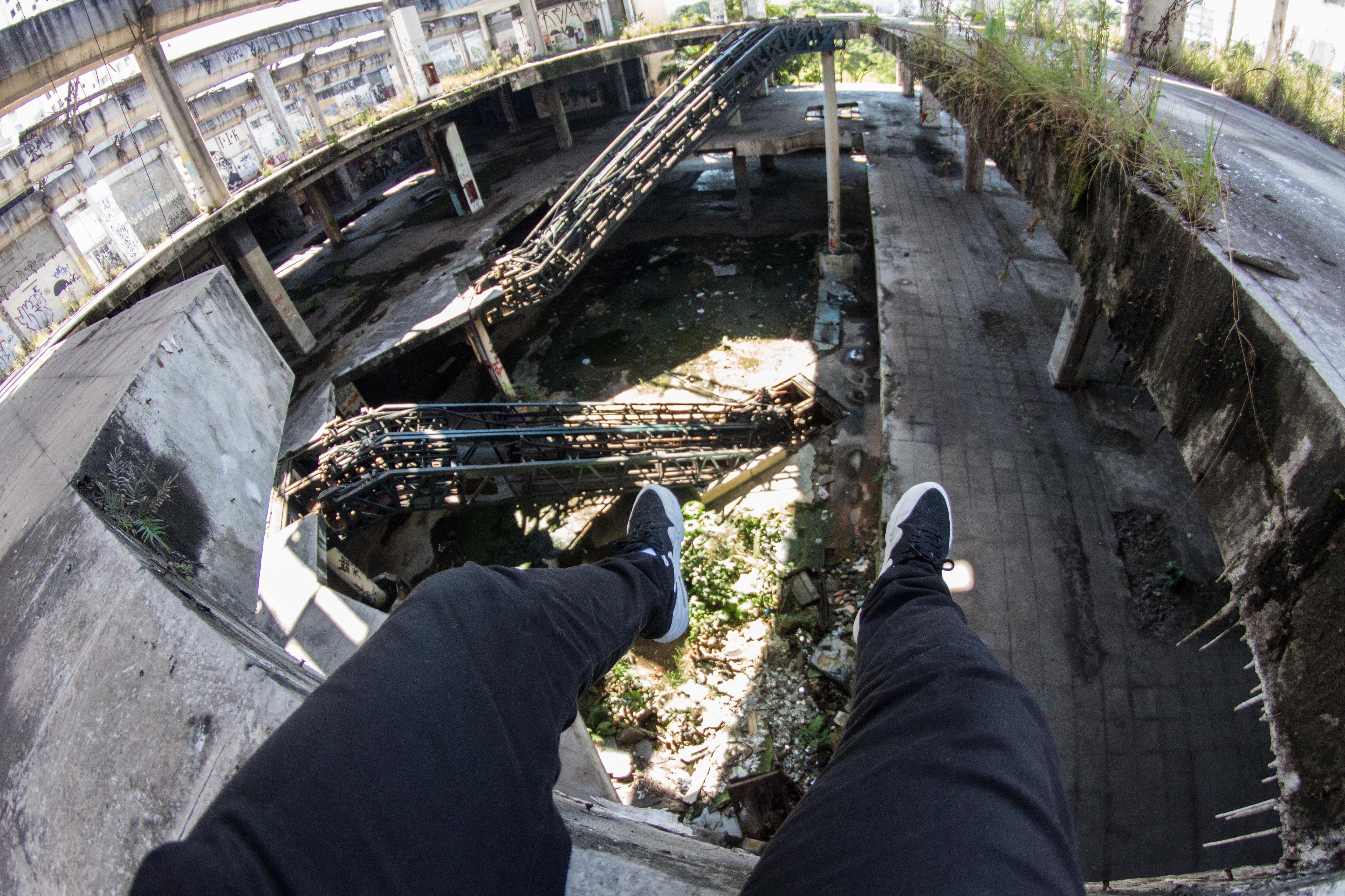 Person Sitting on Gray Concrete Ledge