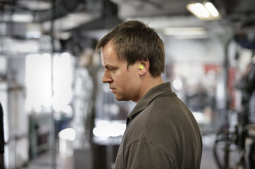 Side view of serious young male fitter in earplugs and dark grey tee shirt standing in workshop