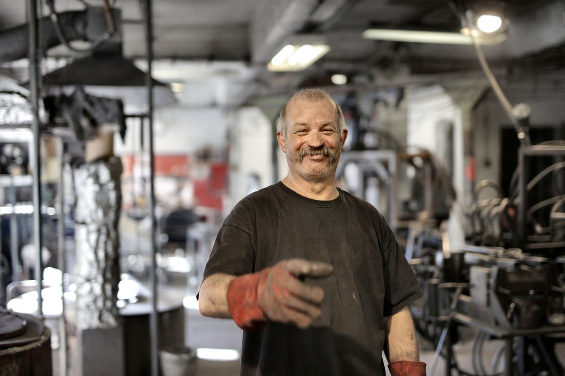 Cheerful senior white hair craftsman in heavy duty gloves laughing in workshop while looking at camera