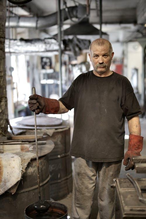Ernsthafter älterer Arbeiter, Der Arbeitsergebnisse Zeigt