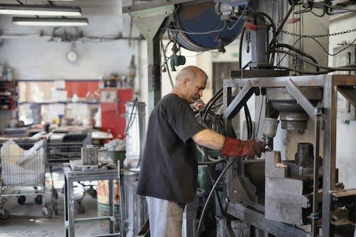 Elderly white hair worker using machine