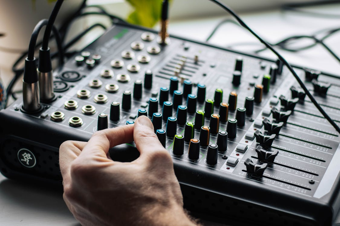 Person Holding Audio Mixer Turned on in Room