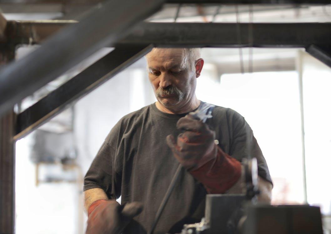 Elderly white hair craftsman with mustache in heavy duty gloves attentively working in workshop