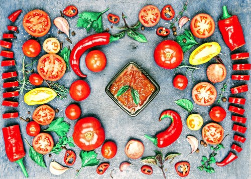 Top view of composition of colorful chili pepper and assorted tomato slices near fresh cilantro and parsley leaves with rosemary and thyme sprigs with bowl of savory sauce in center