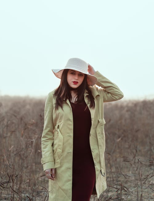 Woman in Beige Coat and Black Skirt Wearing White Fedora Hat Standing on Brown Grass Field