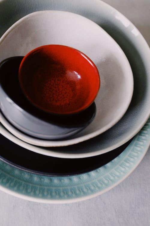 Red Round Ceramic Bowl on White Ceramic Plate
