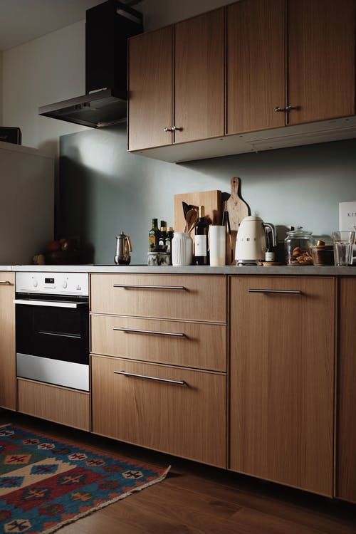 Interior design of spacious apartment kitchen with wooden cupboards and various products placed on table in light home