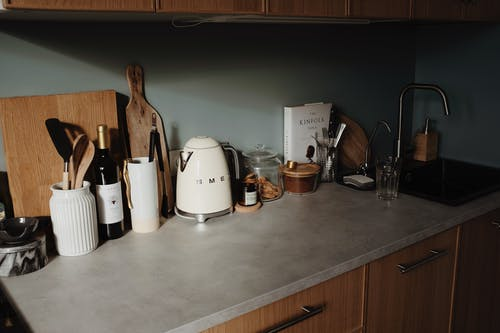 Modern kitchen counter with utensils and cooking equipment near wall