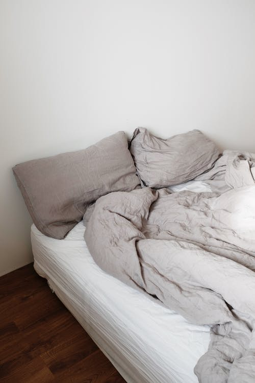 Unmade bed with pillows and blanket in light bedroom