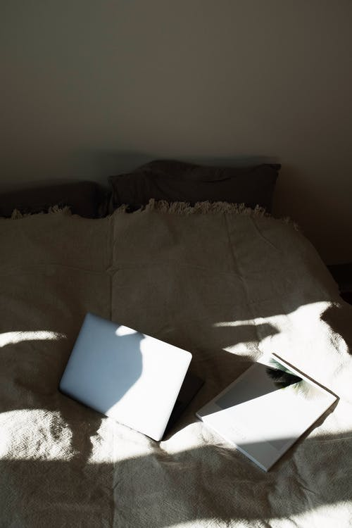 Top view of laptop and book placed on soft blanket on comfortable bed in morning light in modern bedroom