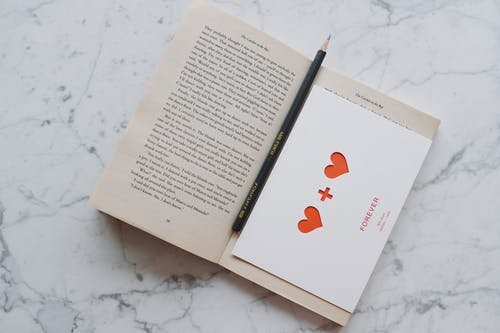 Top view of opened novel book with pencil and romantic postcard placed on white marble surface