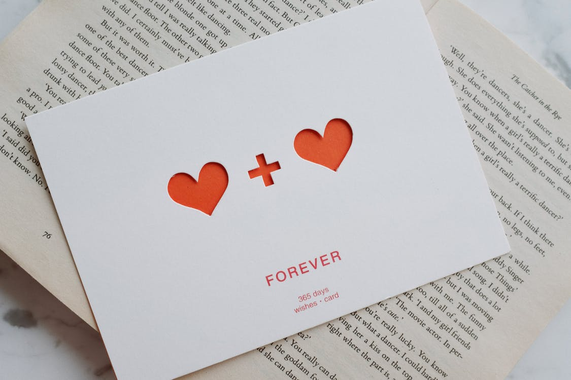 Top view of white paper postcard with cutout red hearts placed on top of opened novel book