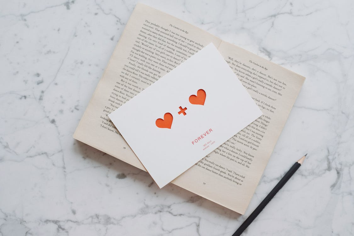 Opened book with pencil and romantic postcard on marble surface