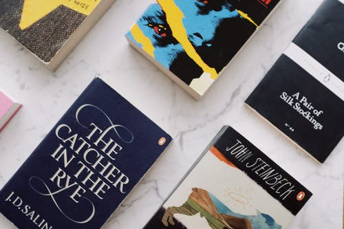 From above of composed colorful paperback novels with colorful covers and inscriptions placed in rows on white marble surface