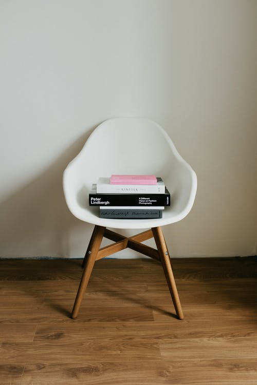 Stylish wooden white chair with stack of books at white wall