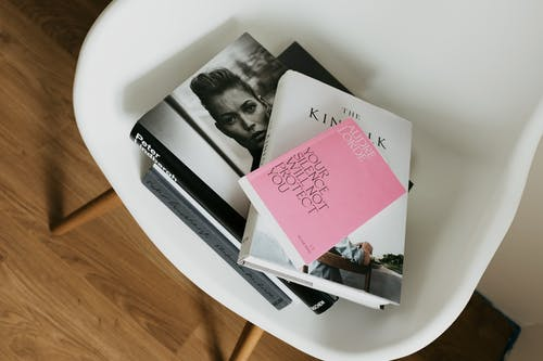 Composed art books on white chair in modern interior