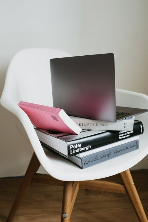 Laptop placed on stack of various books on white chair